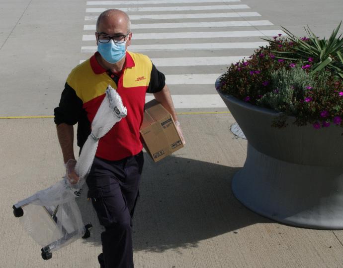 Un repartidor de DHL, realizando la entrega a domicilio de suero